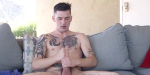 Tattooed gay relaxes outdoors by jacking off his dick