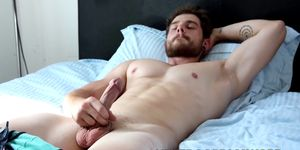 Alluring bearded gay man grabs his massive dick and wanks