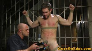 Handsome hunk bound and edged by maledom